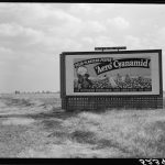 A billboard advertising fertilizer dispersed over the cotton fields by crop-dusting airplanes.