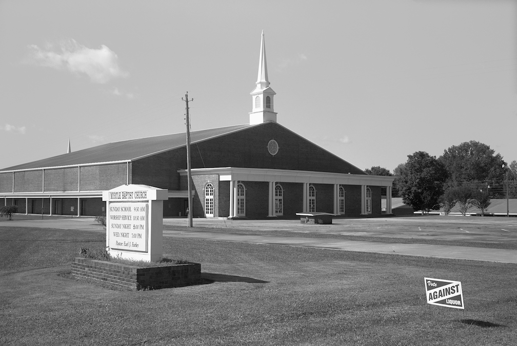 Black and white photo of a church with anti-alcohol sign, Myrtle, MS.