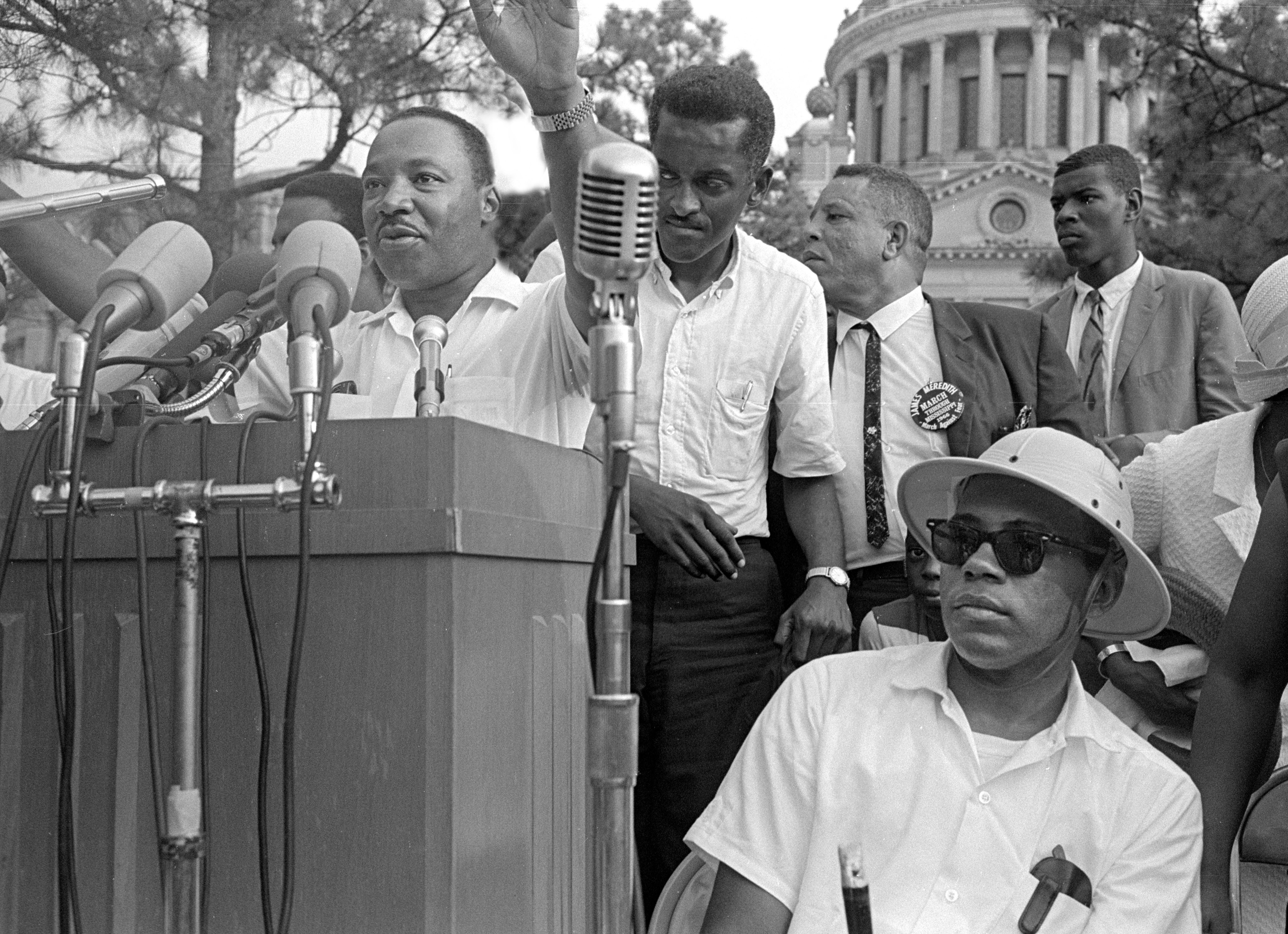The June 26, 1966, March Against Fear rally at the Mississippi state capitol, with Martin Luther King Jr. speaking and James Meredith sitting before the podium (right).